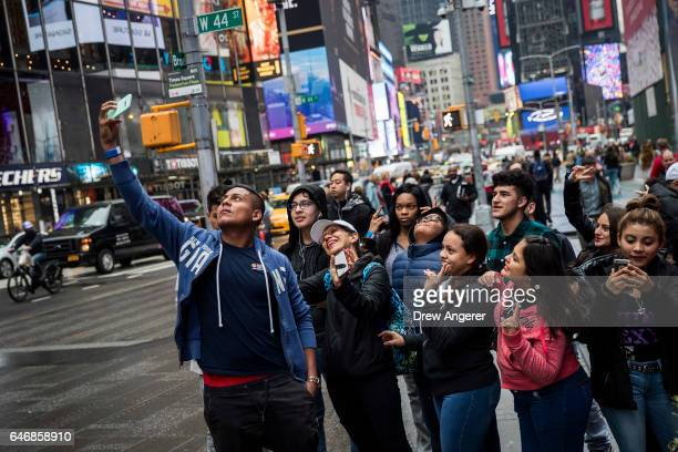 A group of tourists pose for a group picture in Times Square March 1 2017 in New York City NYC Company the city's tourism marking agency released a...