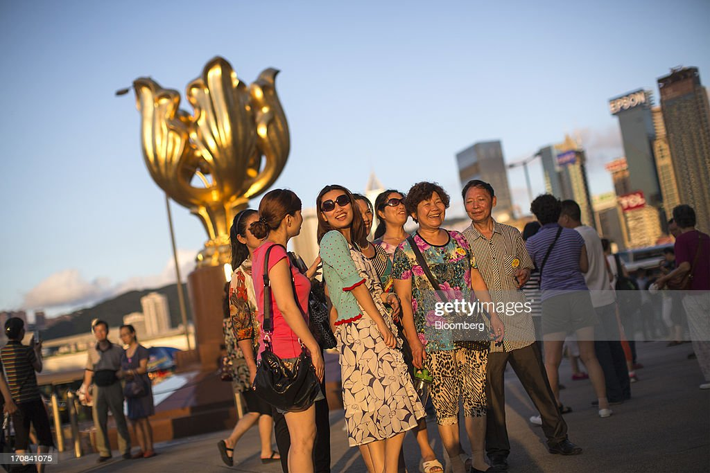 A group of tourists pose for photographs in front of a sculpture of a gilded bauhinia at Golden Bauhinia Square in Hong Kong, China, on Tuesday, June 18, 2013. A shortage of housing, low mortgage costs and a buying spree by mainland Chinese have led home prices to more than double since the beginning of 2009, shrugging off repeated attempts by the government to curb gains amid an outcry over affordability. Photographer: Jerome Favre/Bloomberg via Getty Images