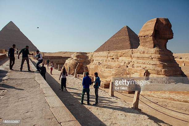 A group of tourists pose for photographs in front of the Sphinx at the Pyramids of Giza compound on October 21 2013 in Cairo Egypt The Pyramids of...