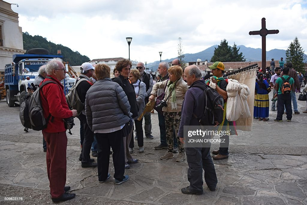 A group of tourists remains outside of the cathedral of San Cristobal de las Casas, Chiapas State, Mexico on February 12, 2016. Pope Francis will arrive in Mexico on Friday, where he will visit until February 17. AFP PHOTO/Johan ORDONEZ / AFP / JOHAN ORDONEZ