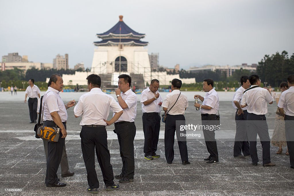A group of tourists smoke in front of the Chiang Kai Shek Memorial Hall plaza in Taipei, Taiwan, on Wednesday, July 24, 2013. Taiwan President Ma Ying-jeou ruled out driving down the Taiwan dollar to boost exports following the currencys rally against the yen and said the government still aims for growth of at least 2 percent this year. Photographer: Jerome Favre/Bloomberg via Getty Images