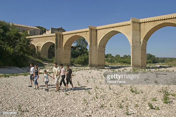 A group of tourists stroll on the parched river Gardon with the Bridge ' Saint Nicolas' in the background August 4 2005 in District of Gard France...