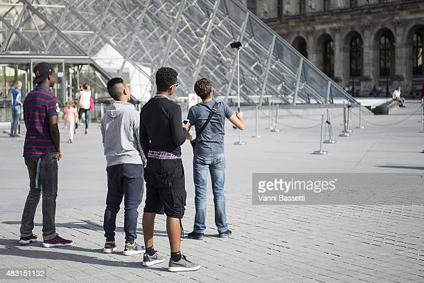 A group of tourists take a selfie using a selfie stick in front of the Louvre Pyramid on August 6 2015 in Paris France Using a selfie stick has...