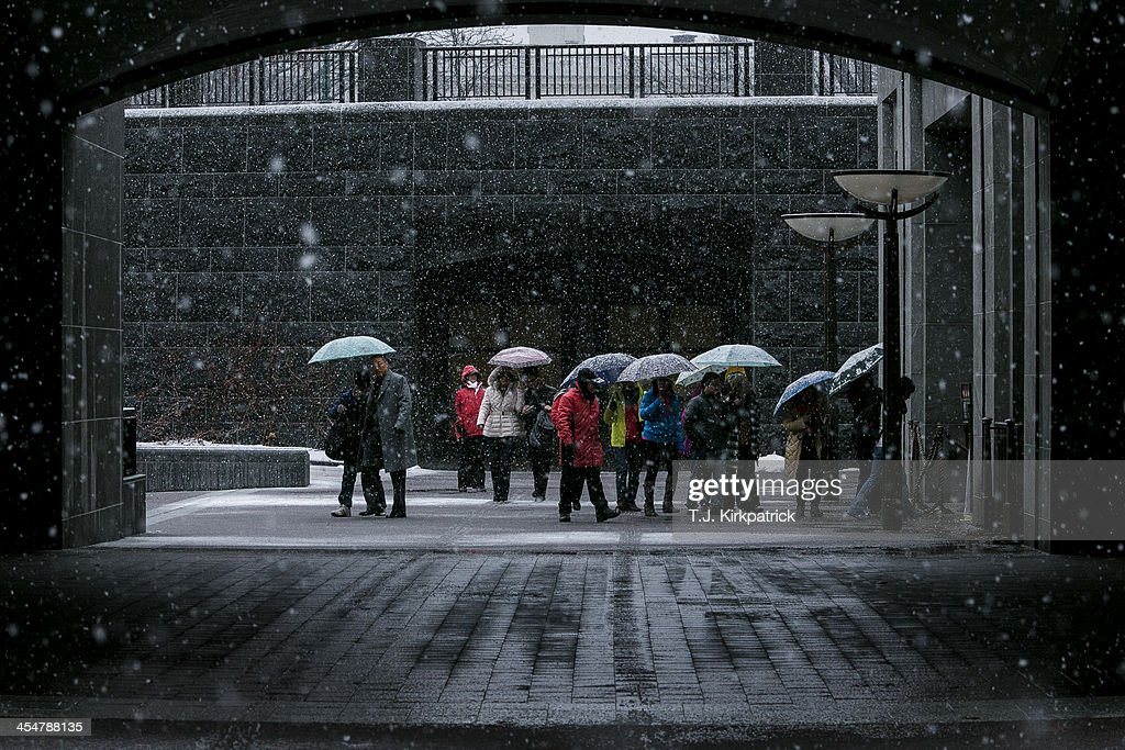 A group of tourists wait to enter the Capitol Visitors Center in the snow on December 10, 2013 in Washington, DC. A winter storm that closed many federal government operations is expected to leave 3-5 inches of snow across the region.