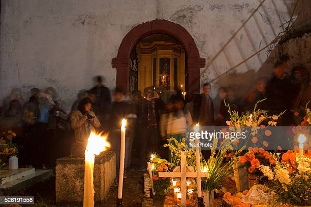 A group of tourists walk and take pictures in the cemetery of Janitzio during the celebration of Day of the Dead on November 1 2015