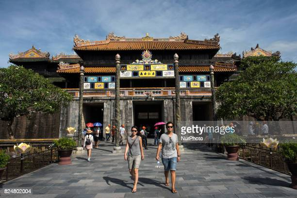 A group of tourists walking through the door of the noon in the Citadel of Hue inspired by the Forbidden City of Beijing is a must for any traveler...