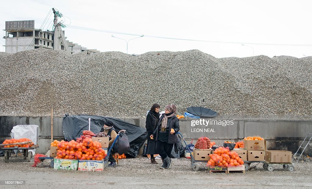A group of traders sell oranges from the roadside in the Sochi district of Adler on February 18, 2013. With a year to go until the Sochi 2014 Winter Games, construction work and development continues as Olympic tests events and World Championship competitions are underway.