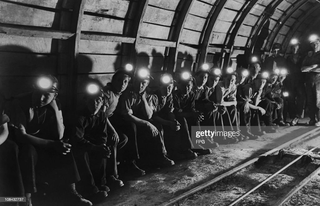A group of trainee miners wait underground for a train that will take them to the coal face at the Markham colliery in Derbyshire, England circa 1950.
