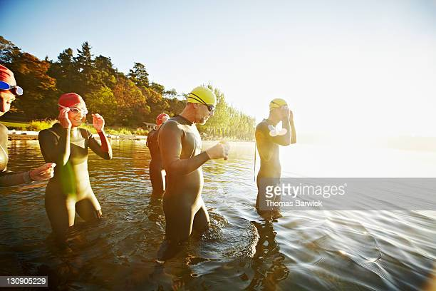 Group of triathletes in water preparing for swim