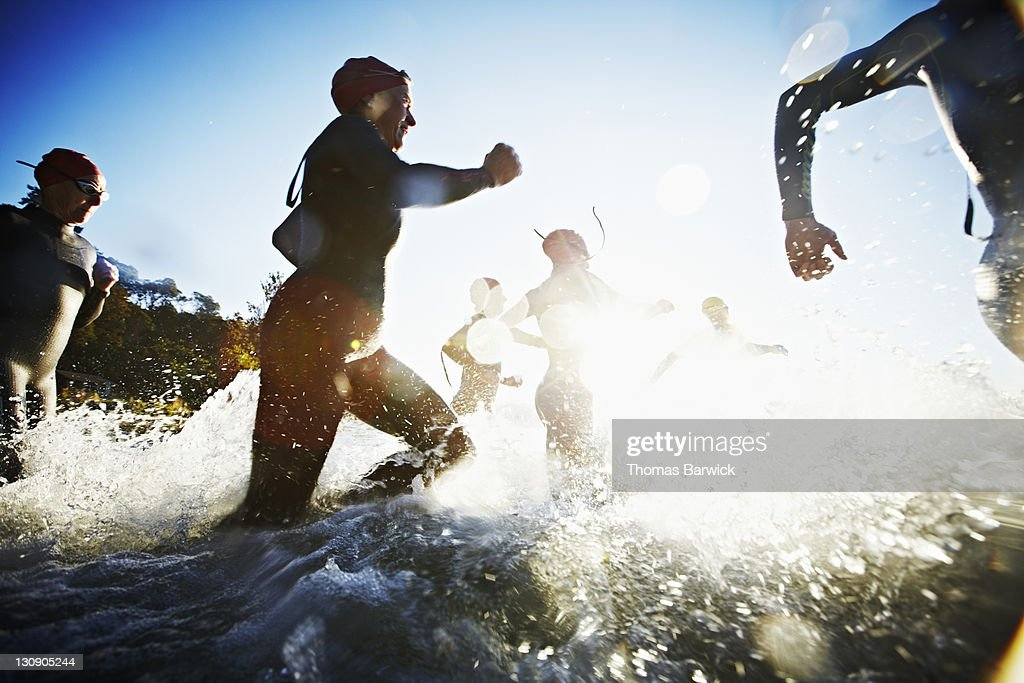 Group of triathletes running into water at sunrise