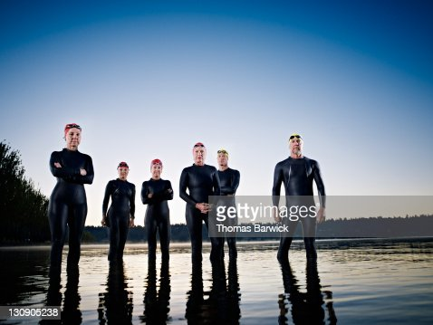 Group of triathletes standing in water at sunrise