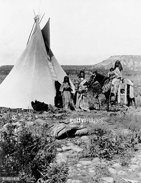 A group of Uinta people identified as Saiar and his family pose outside their tepee on the western slope of the Wastach Mountains Photographed on...