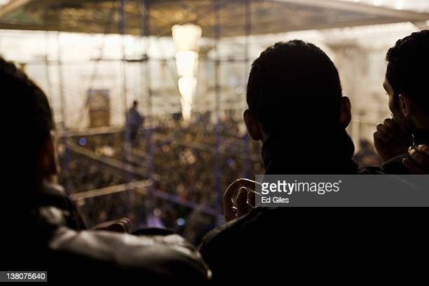 A group of 'ultra' football fans watch as family members and mourners gather at Cairo's railway station as they receive the bodies of 74 football...