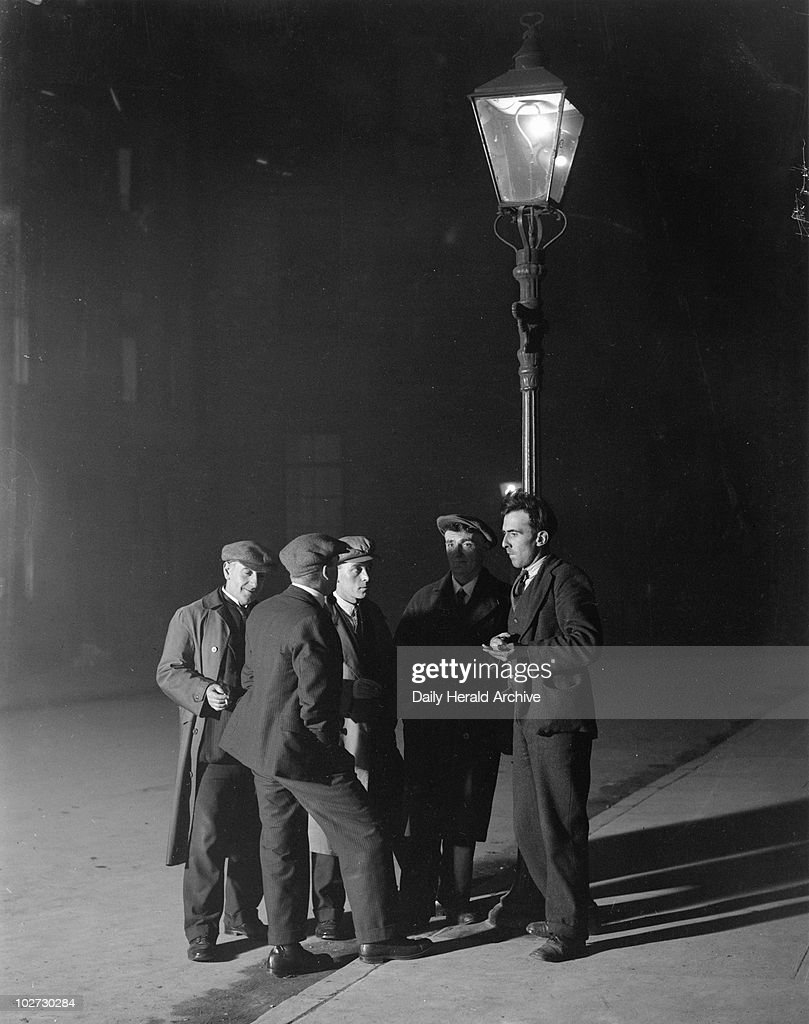 A group of unemployed men gathered round a streetlight, 3 November 1931. A group of unemployed men gathered round a streetlight at night to talk, Govan, Scotland, 3 November 1931. Photograph by James Jarche.