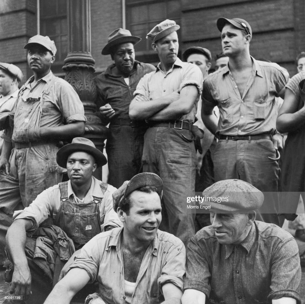 A group of unidentified dock workers wait at a curb, some stand, some seated, neat a street lamp, New York, New York, 1947.