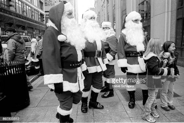A group of unidentified men all dressed in Santa Claus costumes stand with a pair of young girls and other pedestrians on a sidewalk Chicago Illinois...