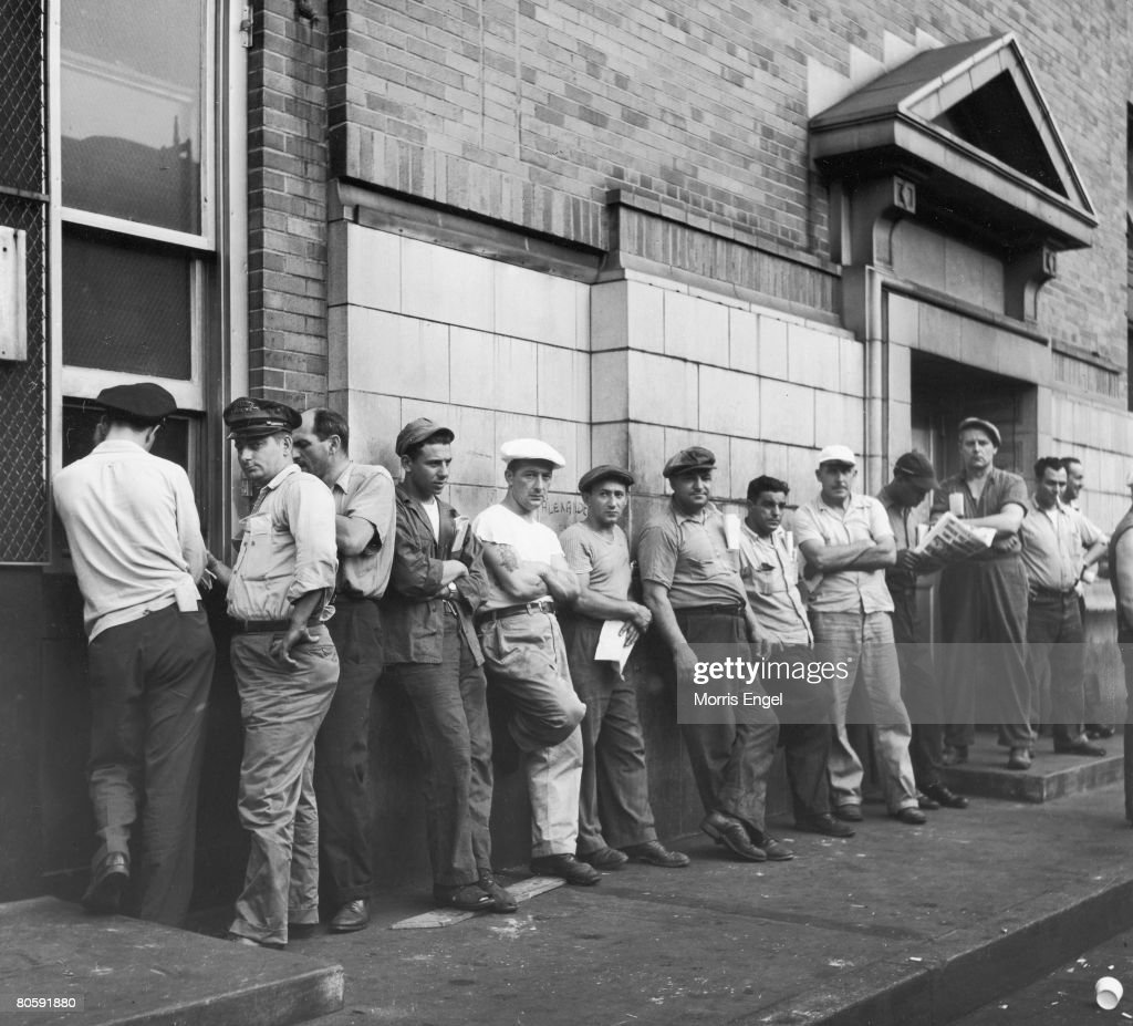 A group of unidentified men, one with a trucking company logo on his cap, lean against a wall as they wait at a pay window to collect their checks, New York, New York, 1947.