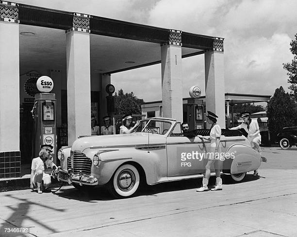 A group of uniformed female attendants cleaning a car for a customer at an Esso station circa 1955