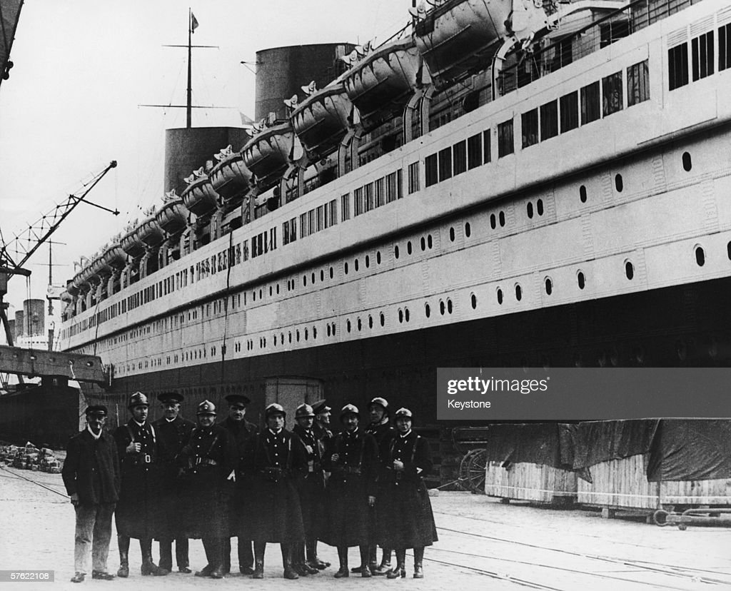 A group of uniformed men on the quayside at Le Havre by the French CGT liner Normandie circa 1935
