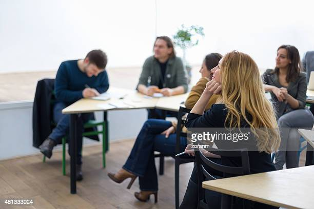 Group of university student sitting in classroom,  listening to