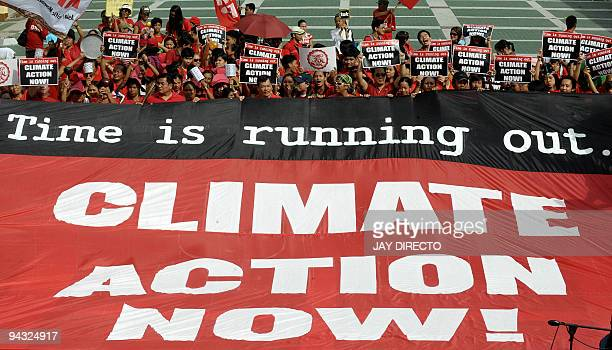 A group of university students and environmental activists hold a banner in support of action against global warming during a protest in Manila on...