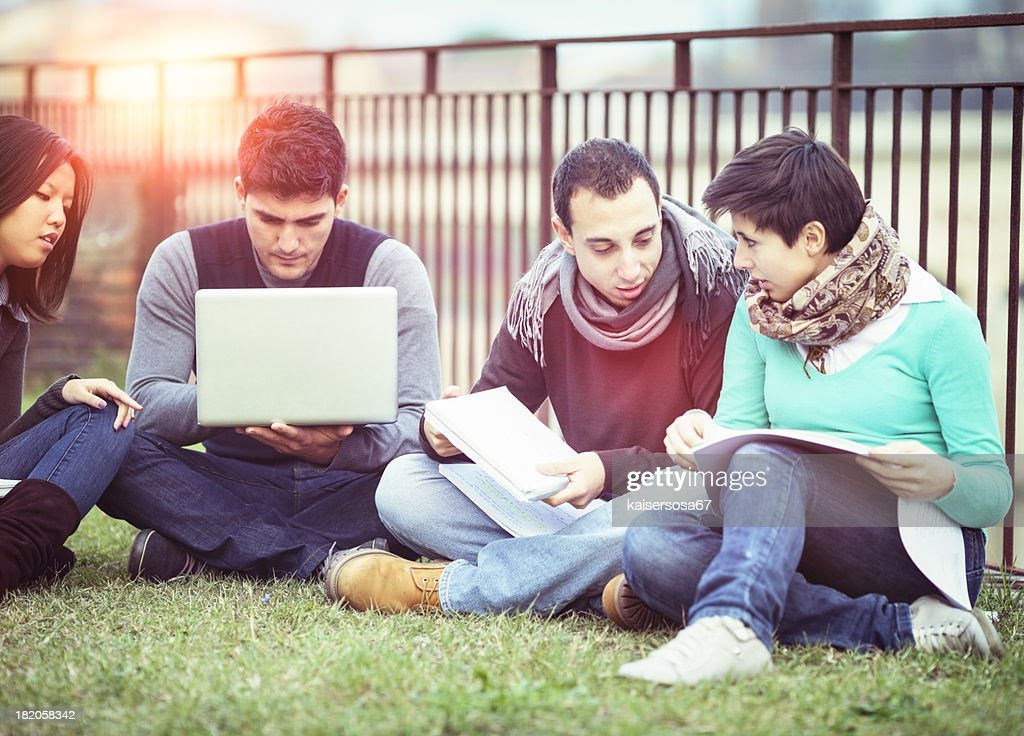 Group of university students using laptop outdoors : Stock Photo