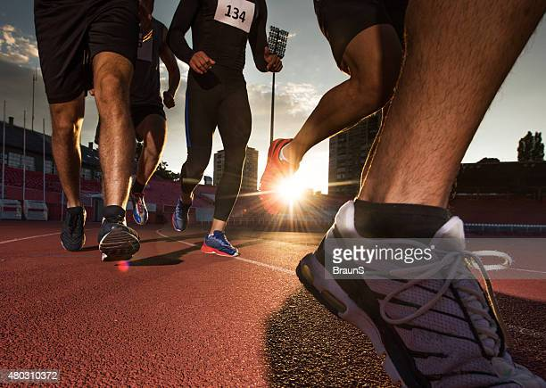 Group of unrecognizable athletes running a marathon at sunset.