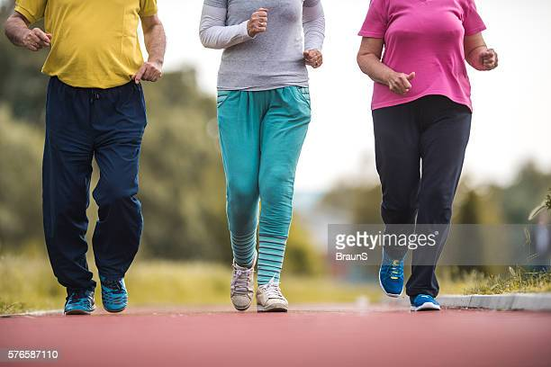 Group of unrecognizable people jogging on running track.