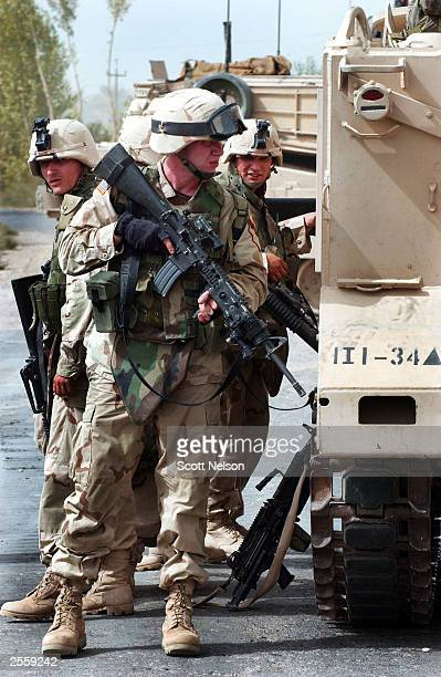 A group of US Army 1st Cavalry Division 1st Battalion 9th Regiment soldiers takes cover from Iraqi insurgents' small arms fire behind an armored...