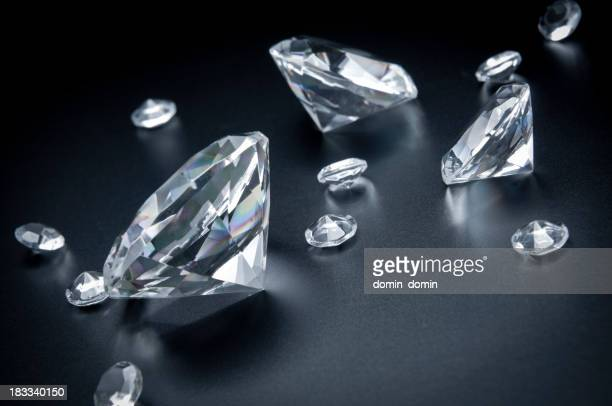 Group of various sized diamonds scattered on black background