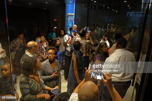 A group of visitors descend in an elevator marked with an African American history timeline as crowds gather to see the grand opening of the...