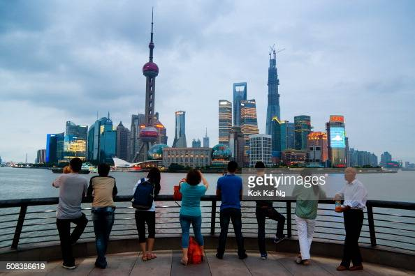 CONTENT] A group of visitors look towards Shanghai's Pudong skyline from the Bund at dusk