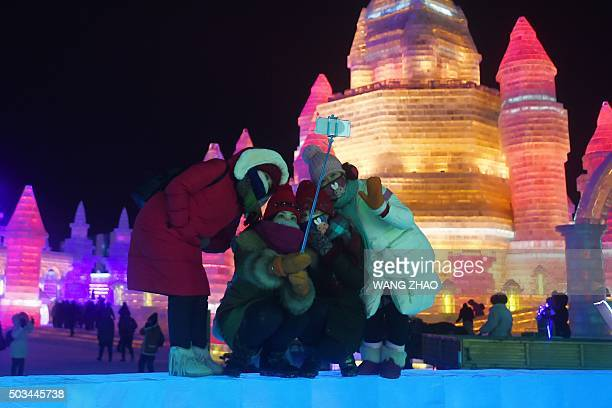 A group of visitors use a mobile phone to take a picture at the China Ice and Snow World during the Harbin International Ice and Snow Festival in...