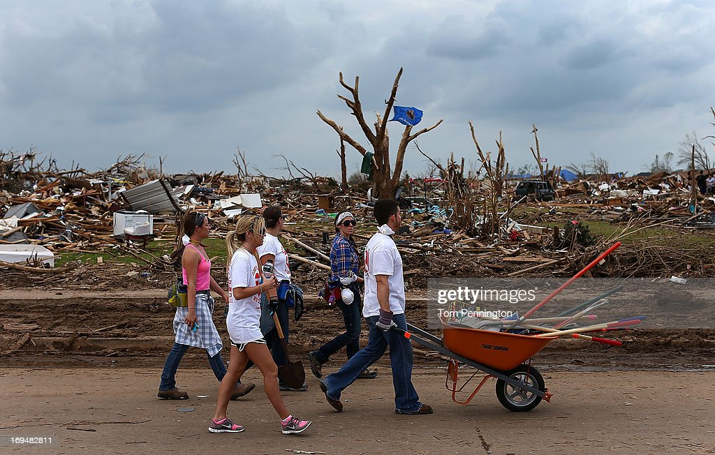 A group of volunteers from Texas make their way through a tornado ravaged neighborhood while helping residents clean up May 25, 2013 in Moore, Oklahoma. The tornado of EF5 strength and two miles wide touched down May 20 killing at least 24 people and leaving behind extensive damage to homes and businesses. U.S. President Barack Obama promised federal aid to supplement state and local recovery efforts.