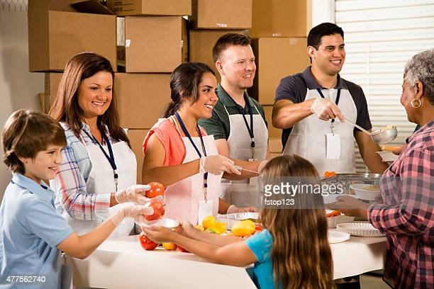 Group of volunteers serve food at community soup kitchen. Charity.