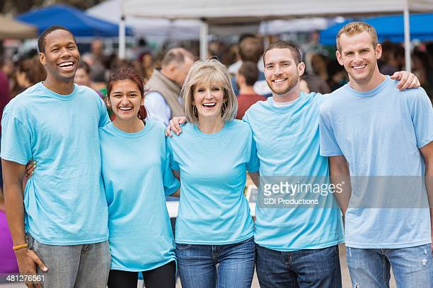 Groupe de volontaires travaillant en plein air ou au marché paysan festival