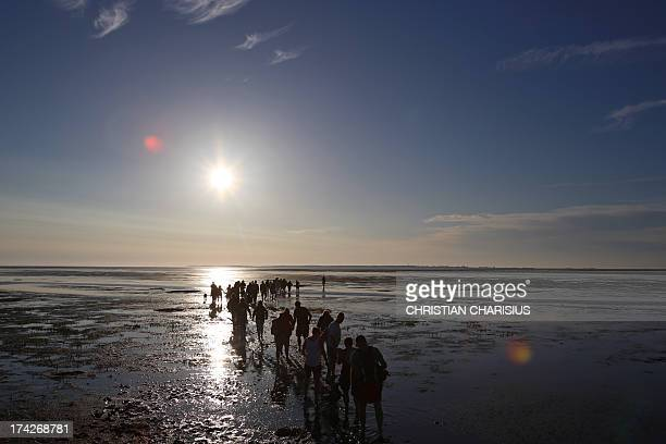 A group of Wadden Sea walkers makes its way across the Wadden Sea from Hallig Langeness to Dagebuell northern Germany on July 22 2013 Meteorologists...