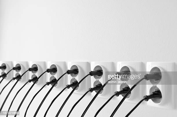 Group of wall outlets with black plugs, cables stucked in