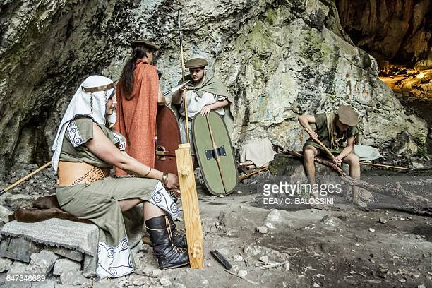 Group of warriors resting in a cave with a woman working on a loom Illyrian civilisation mid3rd century BC Historical reenactment
