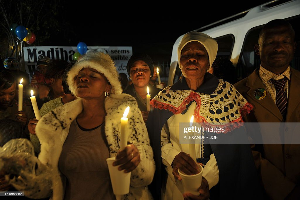 A group of well wishers hold candles as they pray for the recovery of former South African president Nelson Mandela outside the Mediclinic heart hospital in Pretoria on June 26, 2013. Mandela is receiving treatment at the Mediclinic heart hospital in Pretoria. Mandela's close family gathered yesterday at his rural homestead to discuss the failing health of the South African anti-apartheid icon who was fighting for his life in hospital. Messages of support poured in from around the world for the Nobel Peace Prize winner, who spent 27 years behind bars for his struggle under white minority rule and went on to become South Africa's first black president.