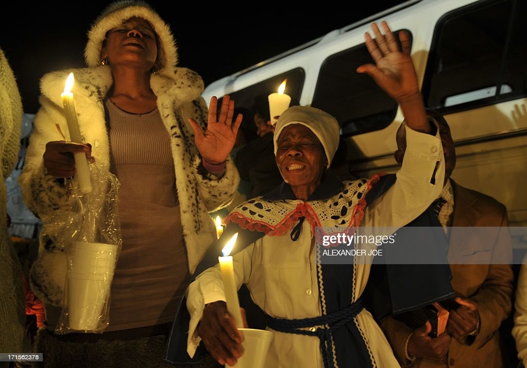 A group of well wishers hold candles as they pray for the recovery of former South African president Nelson Mandela outside the Mediclinic heart hospital in Pretoria on June 26, 2013. Mandela is receiving treatment at the Mediclinic heart hospital in Pretoria. Mandela's close family gathered yesterday at his rural homestead to discuss the failing health of the South African anti-apartheid icon who was fighting for his life in hospital. Messages of support poured in from around the world for the Nobel Peace Prize winner, who spent 27 years behind bars for his struggle under white minority rule and went on to become South Africa's first black president. AFP PHOTO / ALEXANDER JOE