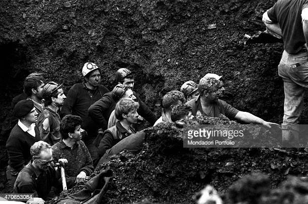 'A group of Welsh miners and volunteers with faces covered in mud work on the deep layer of silt and debris that a landslide poured over their...