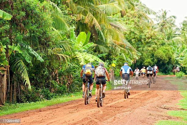 Grupo de la zona oeste de ciclismo de montaña en una carretera de tierra, Camboya