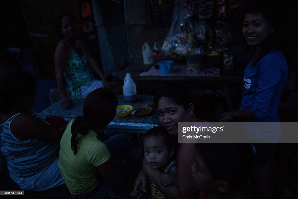 A group of woman chat and relax in darkness due to limited electricity in the coastal area renamed by residents ' Yolanda Village' on April 20, 2014 in Tacloban, Leyte, Philippines. People continue to rebuild their lives five months after Typhoon Haiyan struck the coast on November 8, 2013, leaving more than 6000 dead and many more homeless. Although many businesses and services are functioning, electricity and housing continue to be the main issues, with many residents still living in temporary housing conditions due to 'No Build' areas preventing them from rebuilding their homes. This week marks Holy Week across the Philippines and will see many people attending religious activities.