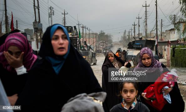 A group of women and children use the opportunity to flee during a lull in the fighting as the Iraqi Special Forces 2nd division engage IS fighters...