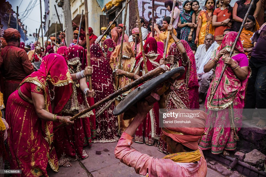 A group of women beat a man holding a shield over his head with sticks during Lathmar Holi celebrations on March 22, 2013 in the village of Nundgaon near Mathura, India. The tradition of playing with colours on Holi draws its roots from a legend of Radha and the Hindu God Krishna. It is believed that young Krishna was jealous of Radha's fair complexion since he himself was himself very dark. After questioning his mother Yashoda on the darkness of his complexion, Yashoda, teasingly asked him to color Radha's face in which ever color he wanted. In a mischievous mood, Krishna applied color on Radha's face. The tradition of applying color on one's beloved is being religiously followed until today.