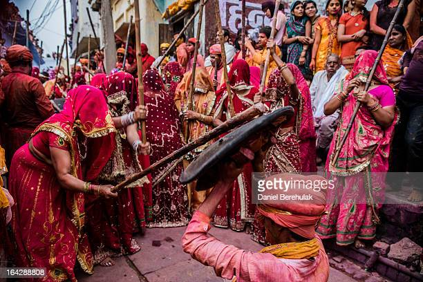 A group of women beat a man holding a shield over his head with sticks during Lathmar Holi celebrations on March 22 2013 in the village of Nundgaon...