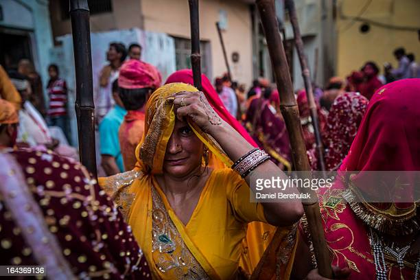 A group of women carry sticks after having participated in the tradition of beating a man holding a shield over his head during Lathmar Holi...