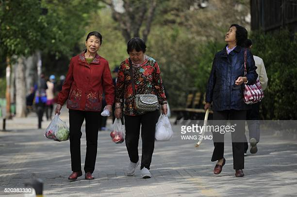A group of women carrying bags of vegetables chat as they walk along a road near a market in Beijing on April 11 2016 China's consumer inflation was...