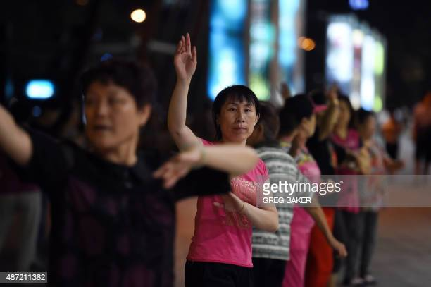 A group of women dance in front of a shopping mall near a residential compound in Beijing on September 7 2015 A spate of noisy disputes between...